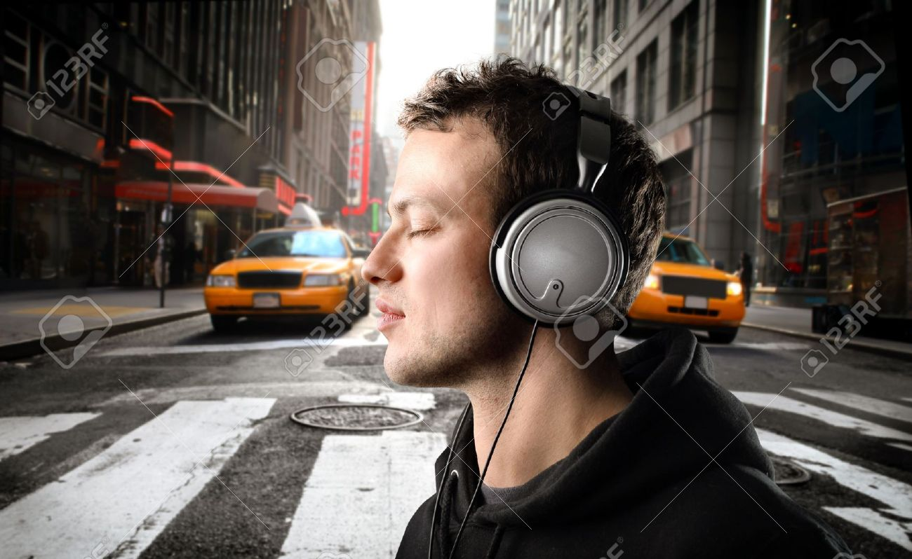 8054447-Young-man-listening-to-music-on-a-city-street-Stock-Photo-music-headphones-listen